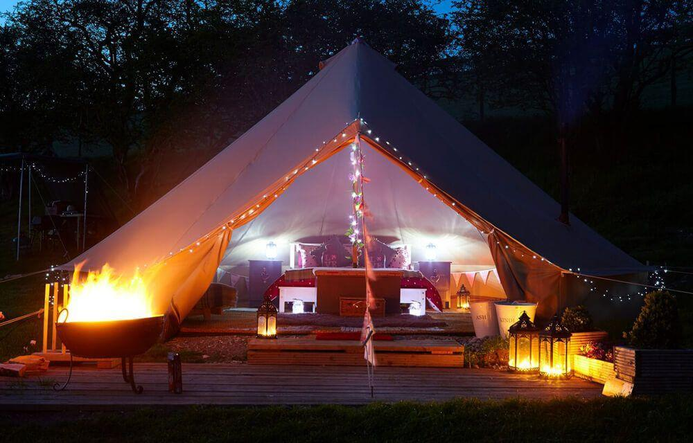 Deluxe Bell Tent at night time with a fire pit!