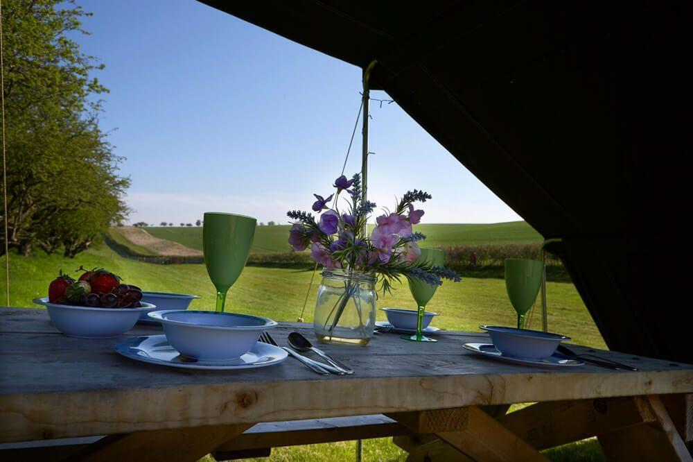 Bell Tent's outdoor picnic bench and canopy area