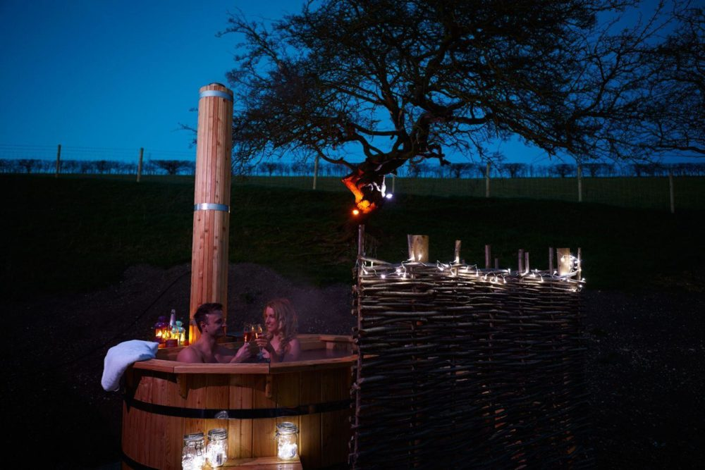 Log Fired Hot Tub with outdoor lanterns and towels